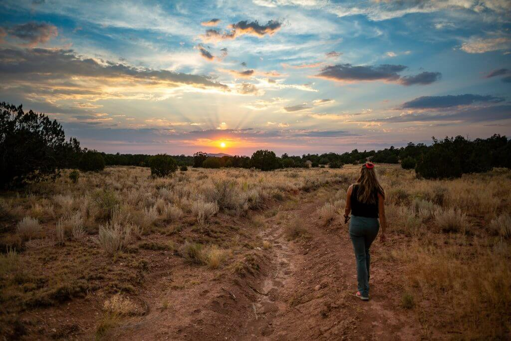 Photo of a Woman Walking at Dusk near the Caverns, Home to Some of the Best Grand Canyon RV Camping.